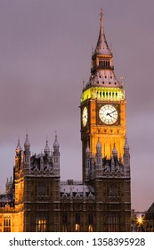 Night view of snow covered Big Ben, closed up, over cloudy sky, seen from Westminster Bridge