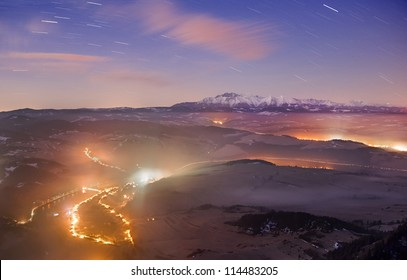 Night view in snowy mountains, with city light in the background.
