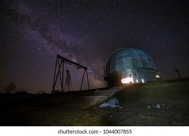 Night view of special astrophysical observatory and crane against background of starry sky with milky way.