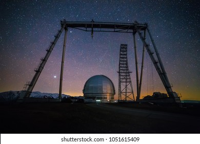 Night view. A special astrophysical observatory and a crane against the background of the starry sky and Caucasian mountains.