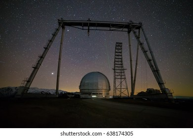 Night view. A special astrophysical observatory and a crane against the background of the starry sky and snowy peaks of the Arkhyz mountains.