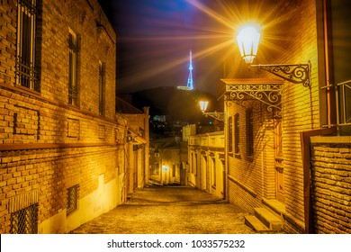Night view to the street in the historic district of Tbilisi Old town with Mtatsminda mountain on background. Tbilisi, Georgia.