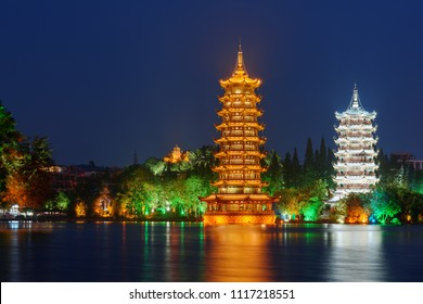 Night view of the Sun and Moon Twin Pagodas at Shanhu Lake (Fir Lake). Gold and Silver Pagodas illuminated at downtown of Guilin, China. Guilin is a popular tourist destination of Asia.