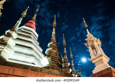 Night view of a temple in Chiang Mai, Thailand, with clouds flying in front of the moon.
