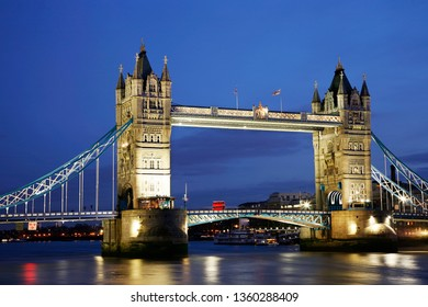 Night view of Tower Bridge at dusk over dramatic blue sky, a red Routemaster bus crossing the river through the bridge.