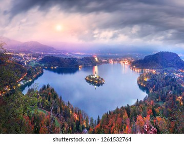 Night view of the town of Bled with a picturesque island among the lake, a castle on a rocky cliff and the outlines of the Julian Alps in the background - all this creates a stunning landscape.
