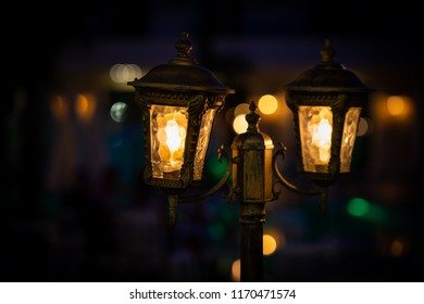 Night view of two orange bright vintage lamp lantern with decoration. Selective focus with soft bokeh.