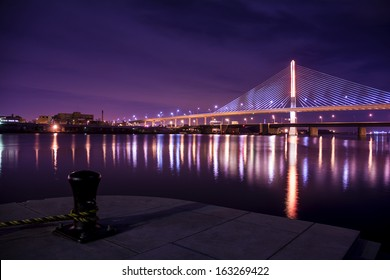 Night view of the Veterans' Glass City Skyway bridge in Toledo Ohio.  The bridges center pylon is lit up with LED lighting and the stainless steel cables are lit with floodlights.