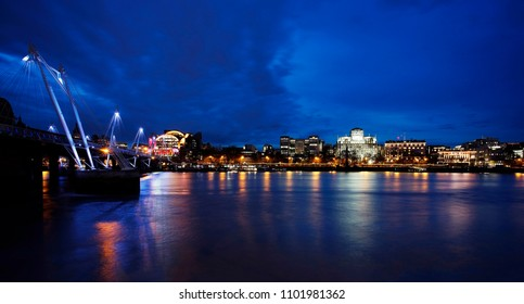 Night View of Victoria Embankment seeing from South Bank. Hungerford Bridge, Embankment station and drmatic blue sky present.