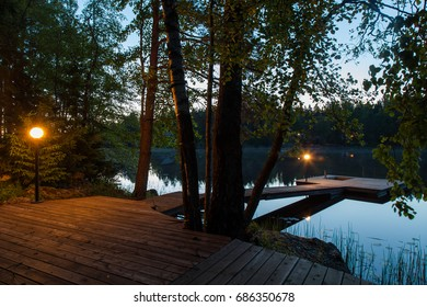 Night view of the wooden pier with a lantern near the lake in Karelia