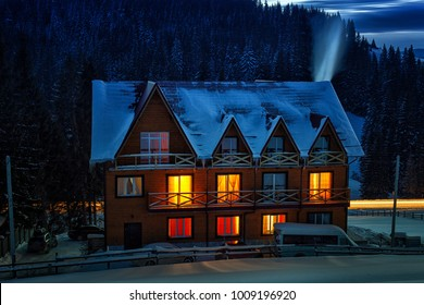 Night view of wooden snowy house with warm lights in windows