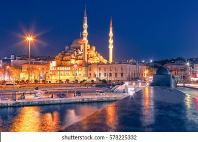 Night view at Yeni Cami Mosque worship place from Galata bridge reflected in water of Golden Horn of Bosporus. Istanbul, Turkey.