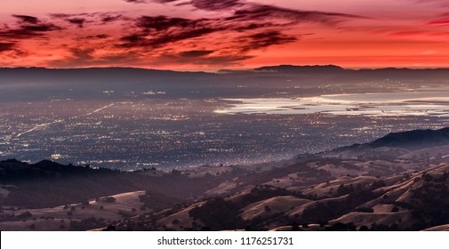 Night views of the cities of Silicon Valley; the city lights of San Jose, Santa Clara and other cities in south San Francisco bay under a red sunset sky; golden hills in the foreground, California