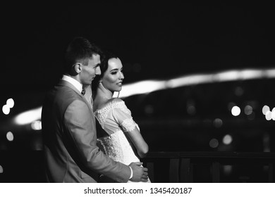Night walk of a young wedding couple on the bridge of the old town of Krakow. Black and white photo option