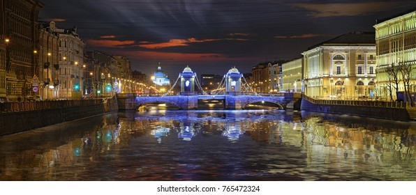 Night wide angle view of Fontanka river embankment and Lomonosov bridge in St. Petersburg