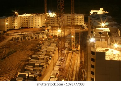 Night works in construction site of a multi storey apartment house with cranes
