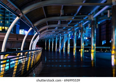 At night,bright light from the street shining to the glossy pole of the curved skywalk between the buildings in the city cause the beautiful color such as yellow gold and blue.At Bangkok Thailand.