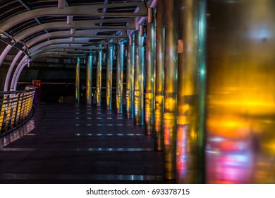 At night,bright light from the street shining to the pole of the curved skywalk between the buildings in the city cause the beautiful color such as yellow gold blue and orange.At Bangkok Thailand.
