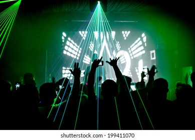 Nightclub man with mobile phone recording lasers at party rave silhouette