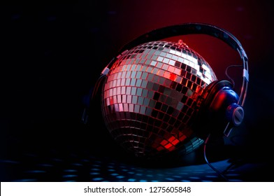 Nightclub music and nightlife concept with a disco ball cover in mirror wearing headphones reflecting the red and blue light in a dark club with copy space