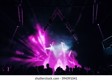 Nightclub party clubbers people with hands in air and pink lasers
