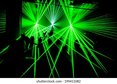 Nightclub party ravers with hands in the air and green lasers silhouette
