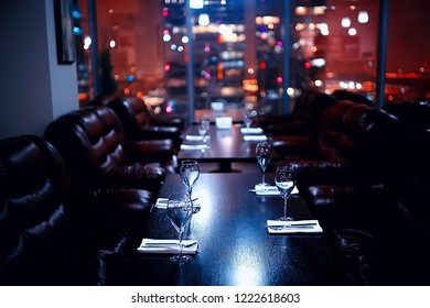 nightclub penthouse in a skyscraper / table setting with glasses and night lights, party, alcohol, the interior of a night club