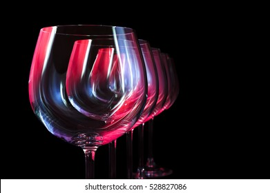 Nightclub wine glasses lit by red, blue, lilac party lights isolated on black background, object in row, nightlife abstraction