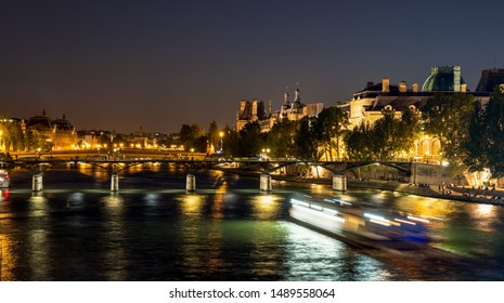 Nightfall over Seine river and illuminated Pont des arts with palais royal and musee d'orsay in background - Paris, France
