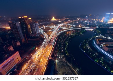 It is at nightfall. There are giant overpasses near a river which shows the high speed of city life.