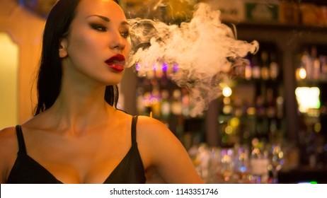 Nightlife. Beautiful Sexy Young Woman with glamorous makeup vaping in Nightclub. Woman exhaling smoke at the bar. Girl smoking vaporizer in Club. Vape Party