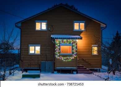 nightly winter landscape with wooden house decorated christmas line of colored bulbs