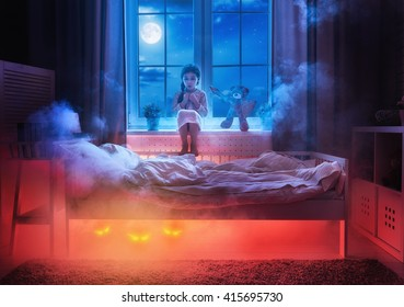 Nightmare for children. Little child girl is afraid of monsters in the dark of night. Frightened little girl and her teddy bear friend are protected against monsters.