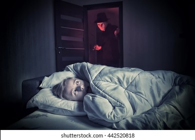 Nightmare. Scared boy lying in the bed while the masked stranger standing in a doorway