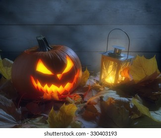 Nightmarish jack o lantern by wooden wall among dried leaves with lighting lantern