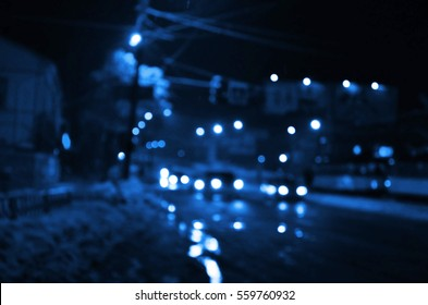 Nights lights of the big city, the blurred night avenue with bokeh traffic lights and headlights of the approaching cars.