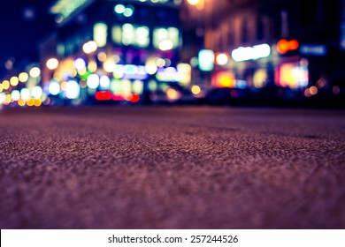 Nights lights of the big city, close up view from asphalt level. Image in yellow-blue toning