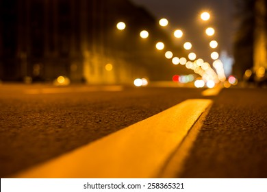 Nights lights of the big city, the night avenue with road markings, close up view from asphalt level