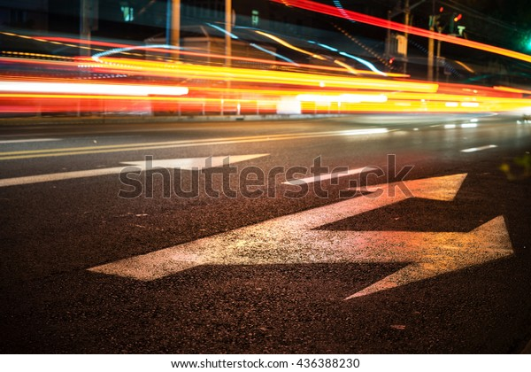 Nights lights of the big city, the night avenue with road markings and headlights of the approaching cars, close up view from asphalt level