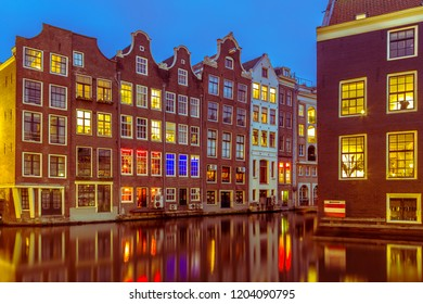 Nightscape of colorful traditional canal houses at night seen from the armbrug on the oudezijds voorburgwal in the UNESCO World Heritage site of Amsterdam