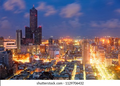Nightscape of Kaohsiung City, a vibrant seaport in South Taiwan, with the landmark 85 Sky Tower standing among modern buildings, street lights dazzling in blue twilight and ships parking in the harbor