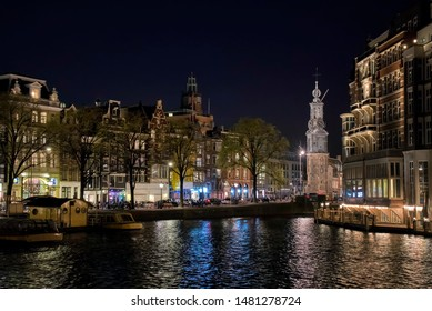 Nightshot of Buildings along the Amstel River in Amsterdam, Holland, with Munttoren