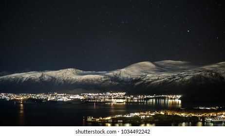 Nightshot of snow covered mountains with fjords and city. Aalesund in Norway. Beautiful destinations in Europe.
