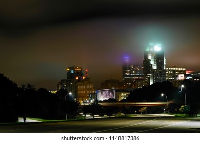 Nighttime cityscape of downtown with the tops of the towers glowing in the the low clouds