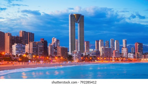 Nighttime illuminated Benidorm cityscape with sandy beaches and modern high housing