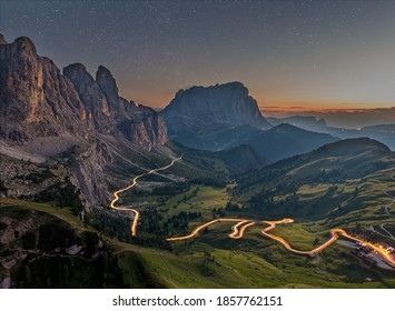 Nighttime image of the Gardena pass with stars and lighttrails in South Tyrol, the Italian Dolomites