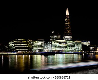 Nighttime image of The Shard and other buildings, including London City Hall, taken across the River Thames from Tower Bridge, London, England, showing lights and reflections in the water, 01/19/2017.