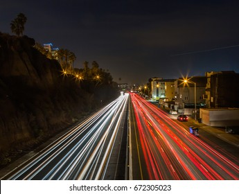 A nighttime, long exposure photo with head and tail lights in Santa Monica Beach of the famous scenic, coastal road called the Pacific Coast Highway that runs along the coast in California.