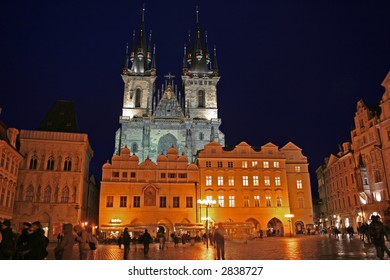 Nighttime shot of Our Lady Before Tyn looming over the lit Old Town Square in Prague