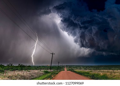 A nighttime, tornadic mezocyclone lightning storm shoots bolt of electricity to the ground and lights up the field and dirt road in Tornado Alley.